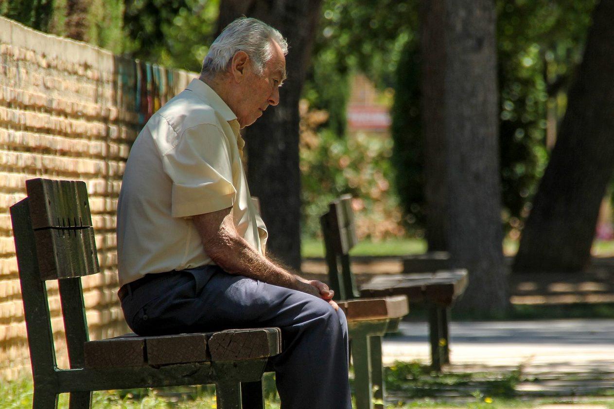 Foto de um senhor de blusa amarela e calça azul escura, sentado em um banco de madeira. Ao lado vemos um muro de tijolos, grama e um caminho. Ao fundo temos outro banco e árvores. Imagem ilustrativa para texto seguro de vida sênior.