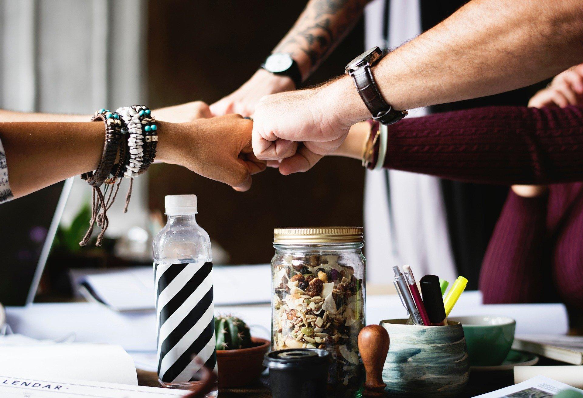 Foto de várias mãos de pessoas diferentes se tocando, em cima de uma mesa com papeis, garrafas, potes com canetas. Imagem ilustrativa para texto seguro vida em grupo.