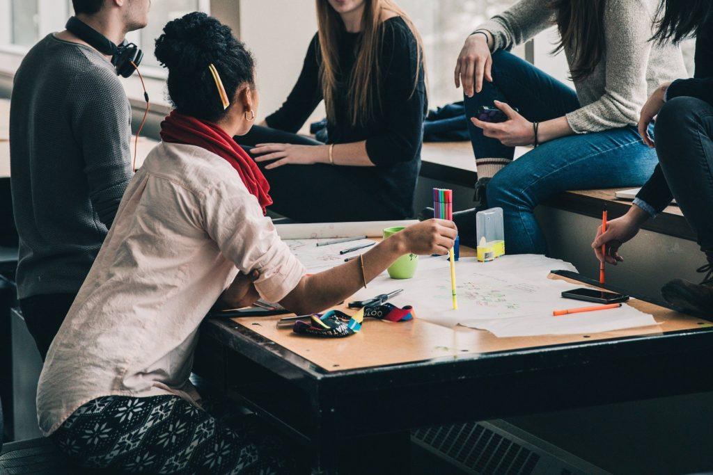 Foto de cinco pessoas reunidas ao redor de uma mesa de madeira com papéis em cima, lápis coloridos, caneca verde e uma janela grande ao fundo. Imagem ilustrativa para texto seguro vida em grupo.