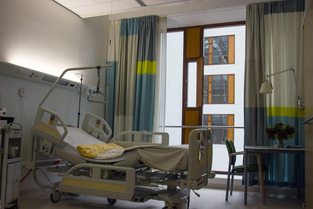 Foto de um quarto de hospital com uma maca cinza no quanto, uma mesa com cadeira no outro e uma janela com cortinas ao fundo. Imagem ilustrativa para texto seguro vida em grupo.