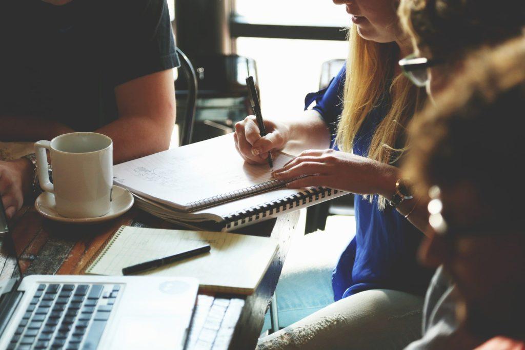 Foto de quatro pessoas reunidas ao redor de uma mesa, ao fundo vemos uma janela. Na mesa temos dois cadernos, uma moça escrevendo em um deles, um computador e xícara.