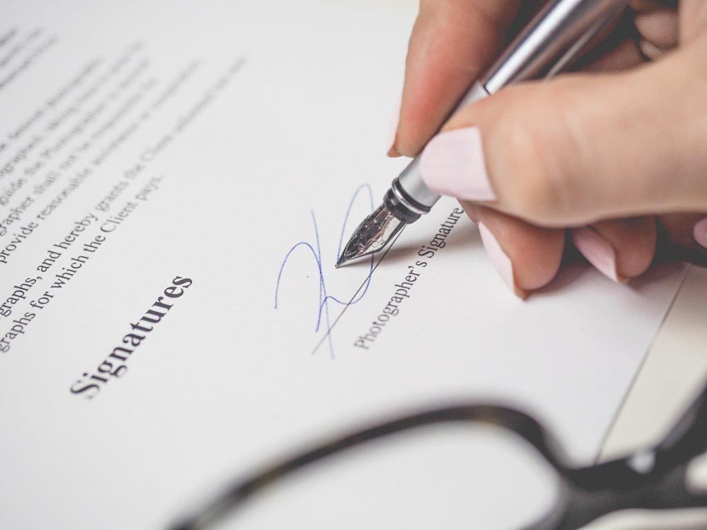 Foto de uma mão segurando uma caneta prata enquanto assina um contrato, vemos parte de um óculos preto também. Ilustração do texto seguro de vida em grupo.