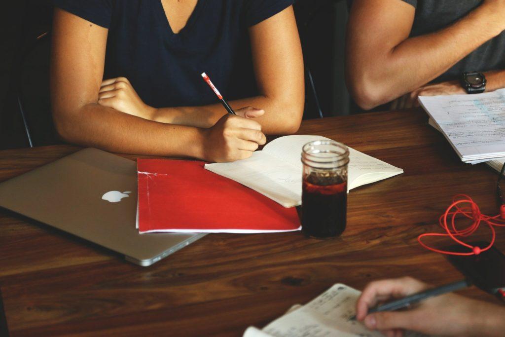 Foto de uma pessoa em uma mesa de madeira com um caderno aberto e uma pasta vermelha ao lado. Temos também um notebook e um copo com bebida. Vemos outra pessoa ao lado com cadernos, uma mão escrevendo em um caderno na frente. Ilustração do texto seguro de vida em grupo.