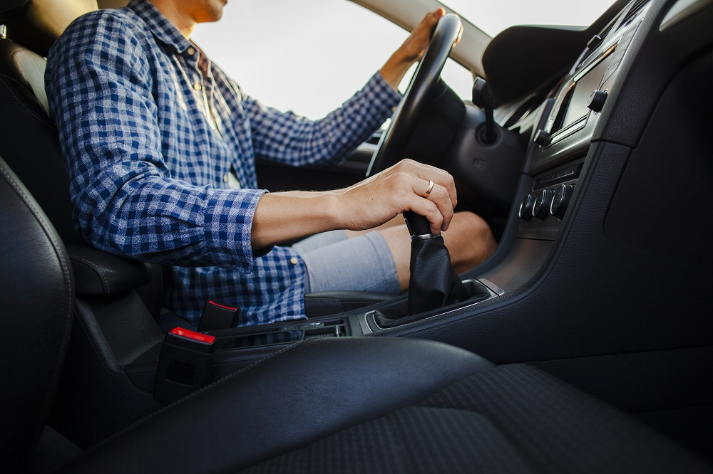 Homem de blusa azul xadrez dirigindo um carro com o interior todo preto. Ele está com uma mão no volante e outra no câmbio. Imagem ilustrativa para texto seguro auto popular.