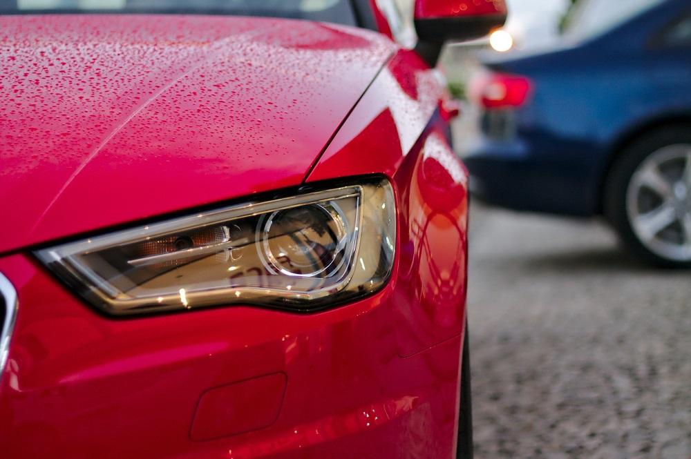 Foto focada no farol direito de um carro vermelho.  Ao fundo vemos a traseira de um carro azul. Imagem ilustrativa para texto seguro auto popular.