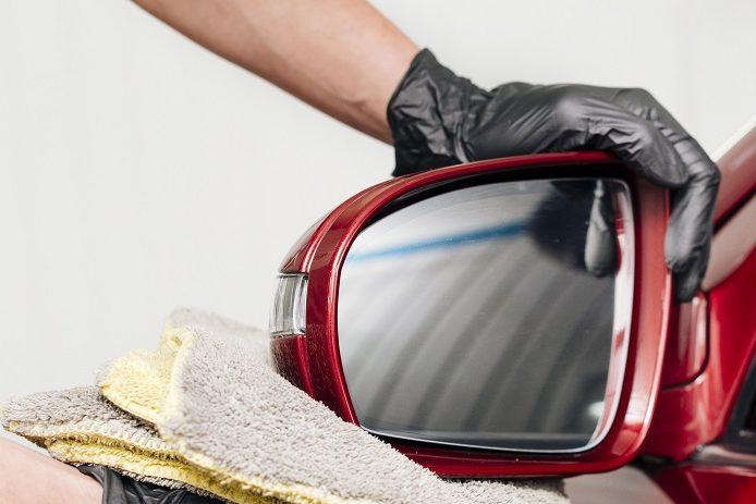 Foto de uma mão com luvas, segurando uma toalha cinza enquanto apoia um retrovisor de carro vermelho. Imagem ilustrativa para texto seguro auto popular.