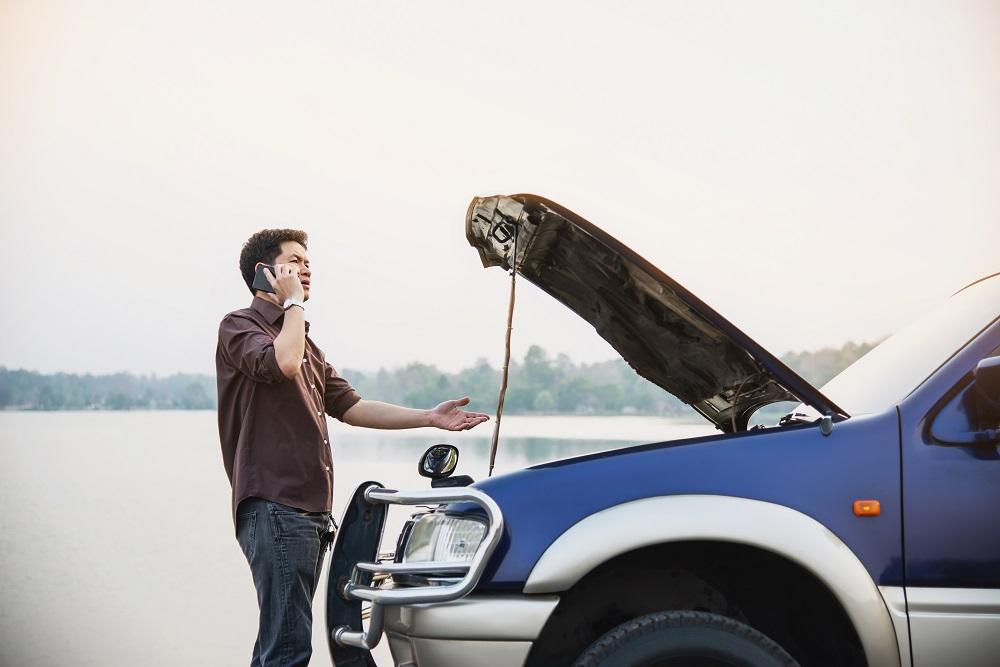 Homem de blusa marrom e calça jeans, fazendo uma ligação em frente a um carro azul estragado com o capô levantado. Ao fundo temos um lago e árvores.