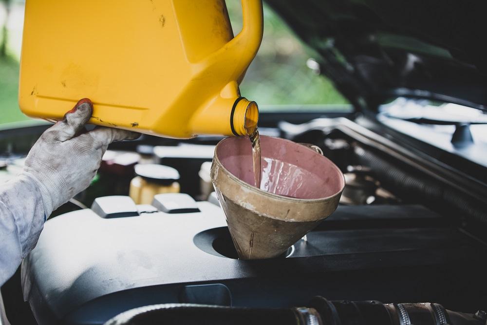 Foto de um mecânico de luva branca, segurando um galão de óleo amarelo, enquanto utiliza um funil para colocar a substância no carro. Ao fundo vemos outras peças do motor e um fundo verde.