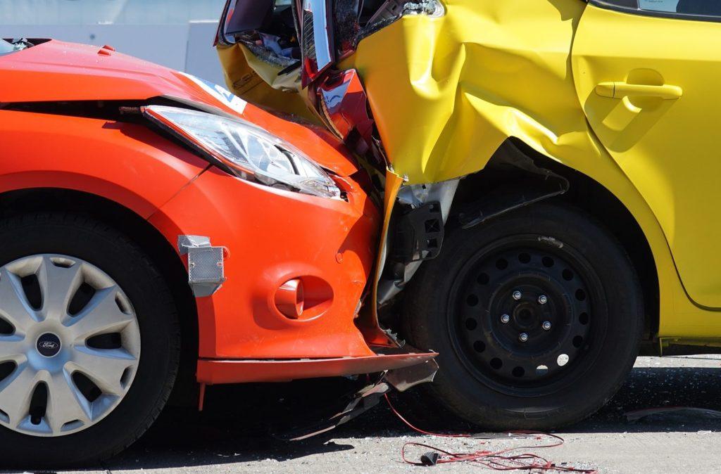 Foto de um carro vermelho, batendo um carro amarelo. Vemos peças amassadas e destroços no asfalto.