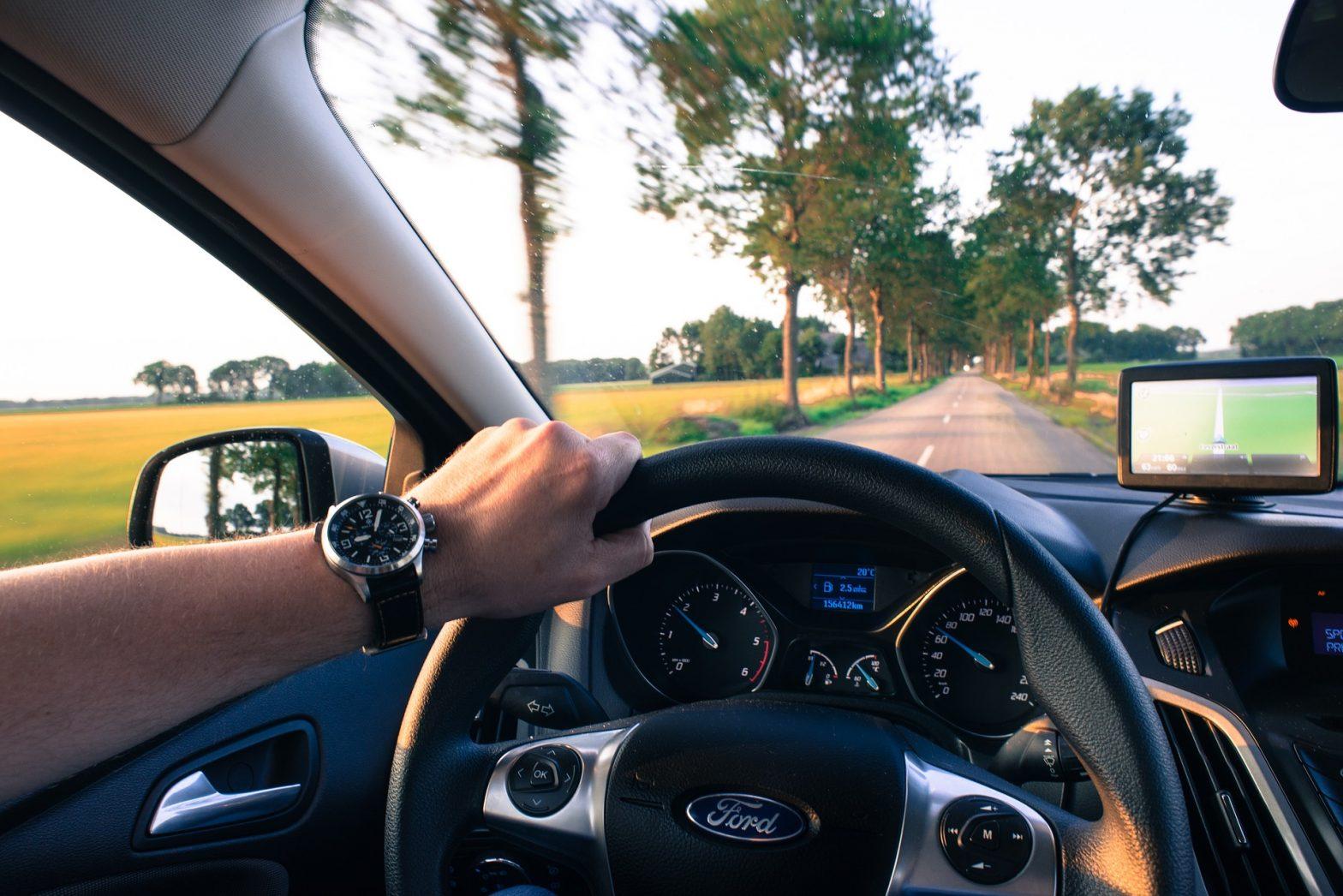 Foto da mão de uma pessoa segurando um volante enquanto dirige em uma estrada com várias árvores. Imagem ilustrativa para o texto perda de cobertura do seguro auto.
