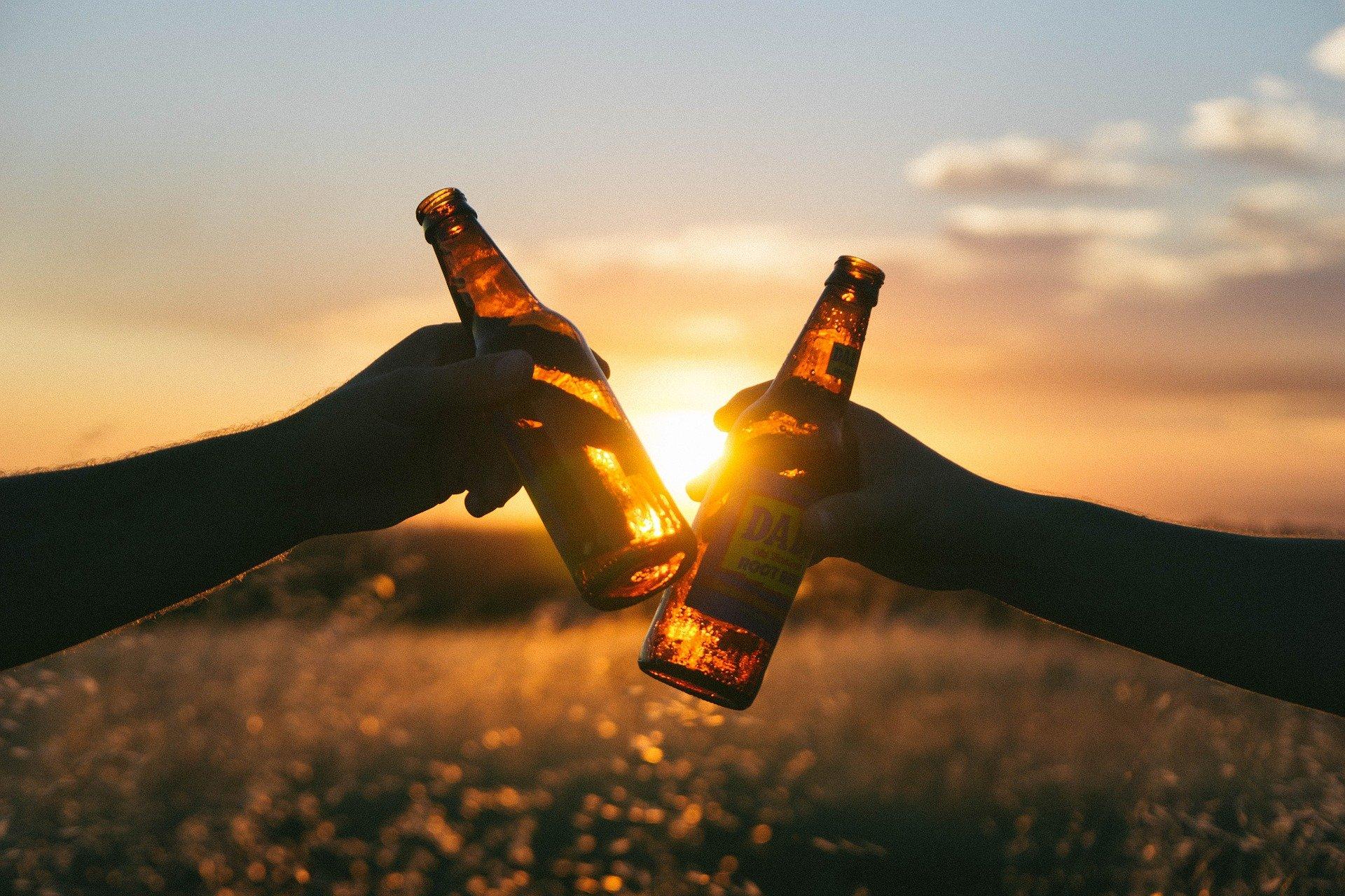 Foto da mãos de duas pessoas segurando garrafas de cerveja e brindando. Imagem ilustrativa para o texto perda de cobertura do seguro auto.