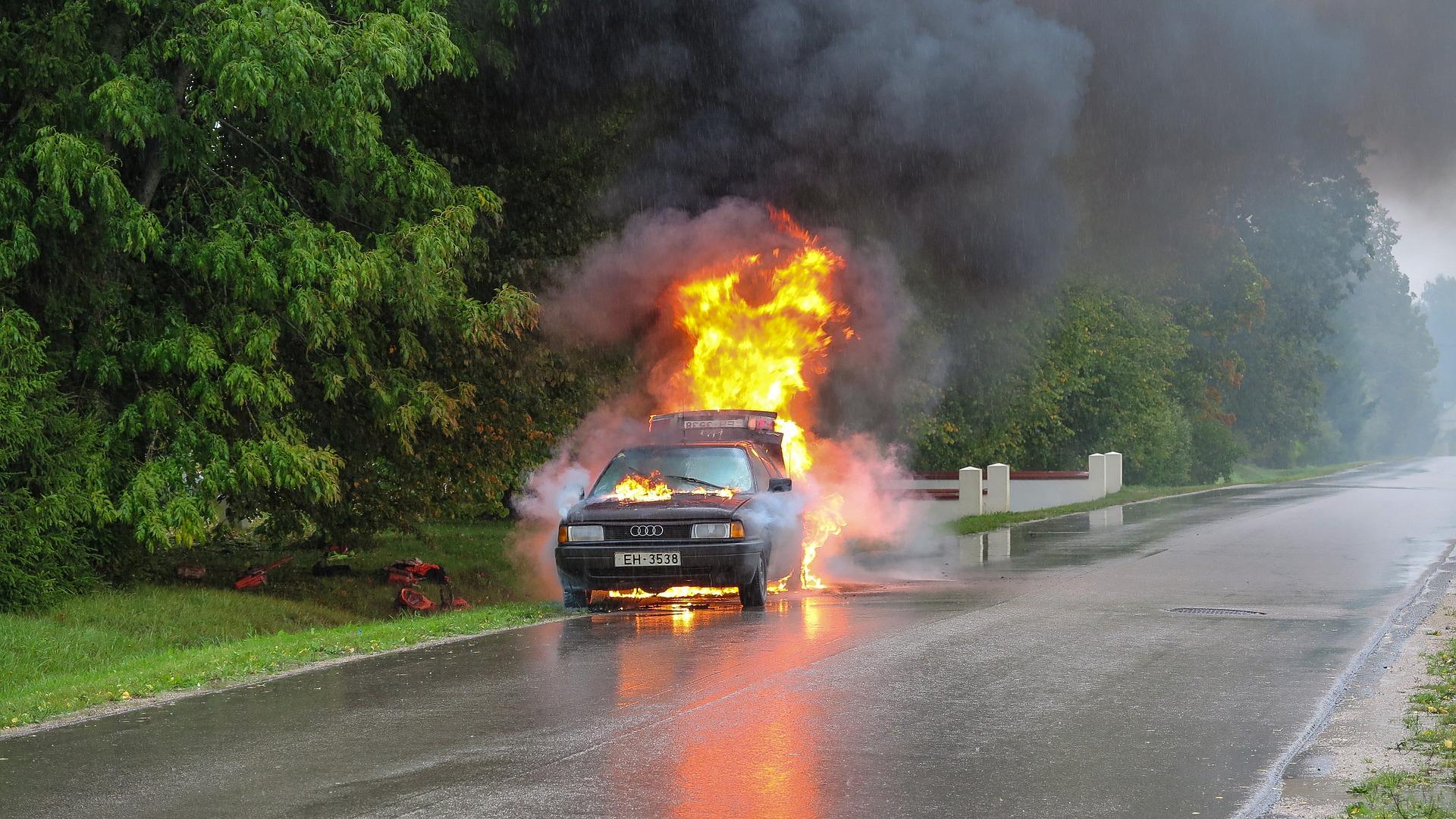 Foto de um carro pegando fogo no meio de uma estrada com árvores ao redor. Imagem ilustrativa para o texto perda de cobertura do seguro auto.