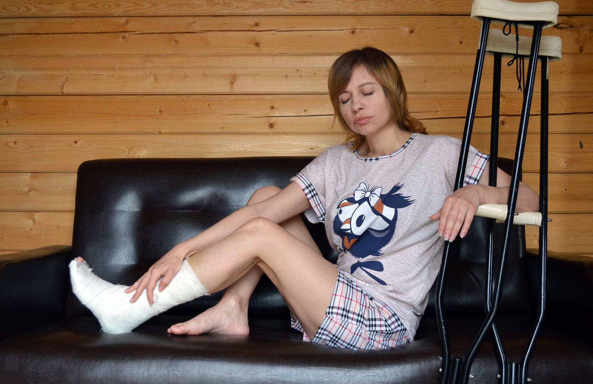 Foto de uma mulher sentada em um sofá com pé engessado, enquanto segura muleta. Imagem ilustrativa para texto segurado e beneficiário.