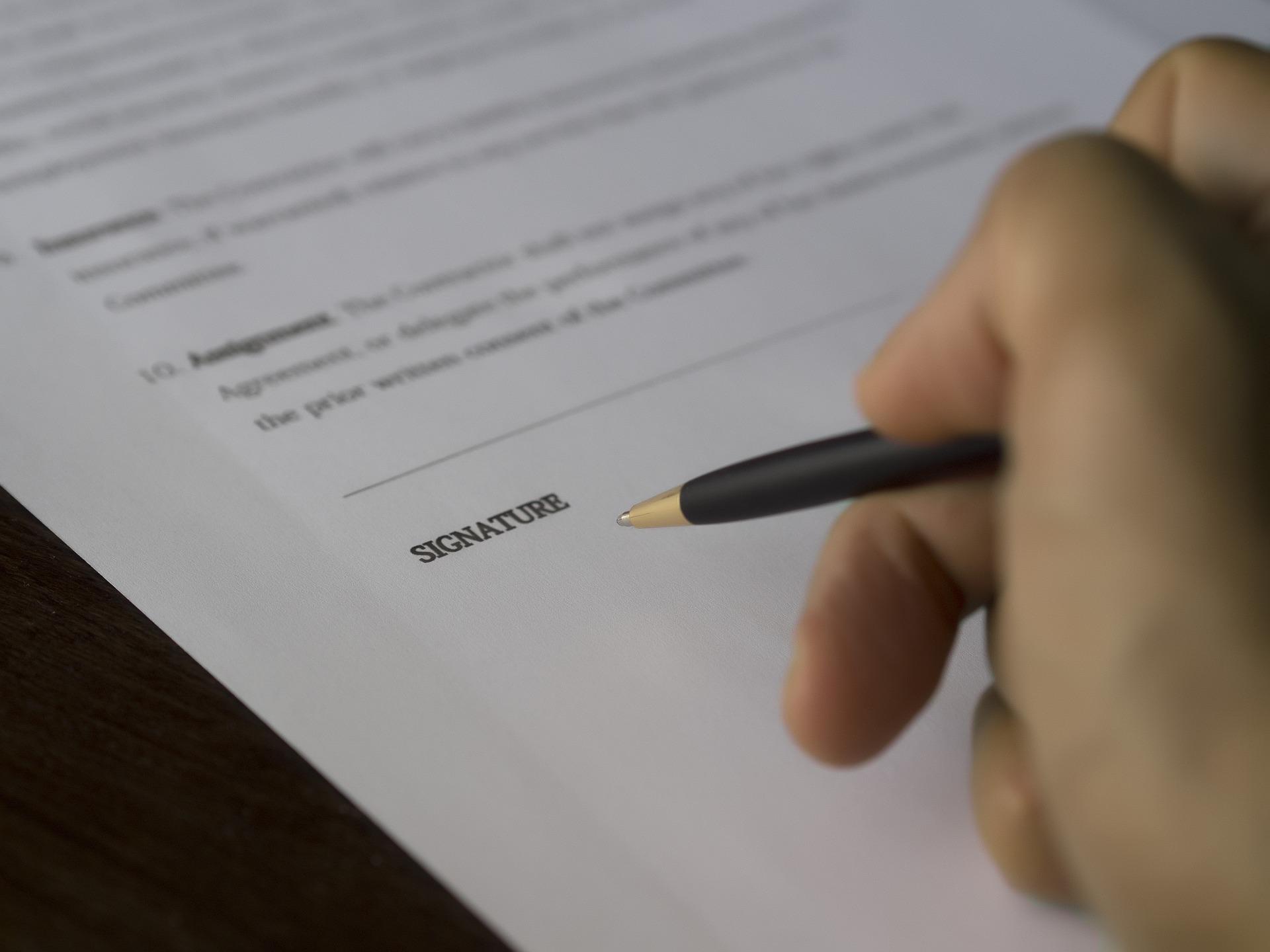 Foto da mão de uma pessoa segurando uma caneta para assinar documento. Imagem ilustrativa para texto segurado e beneficiário.
