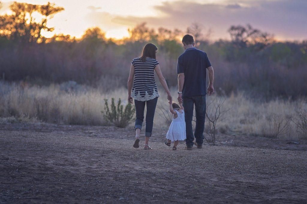Foto de uma família em um campo, com uma mulher e um homem dando a mão para uma criança no meio. Imagem ilustrativa para o texto segurado e beneficiário.
