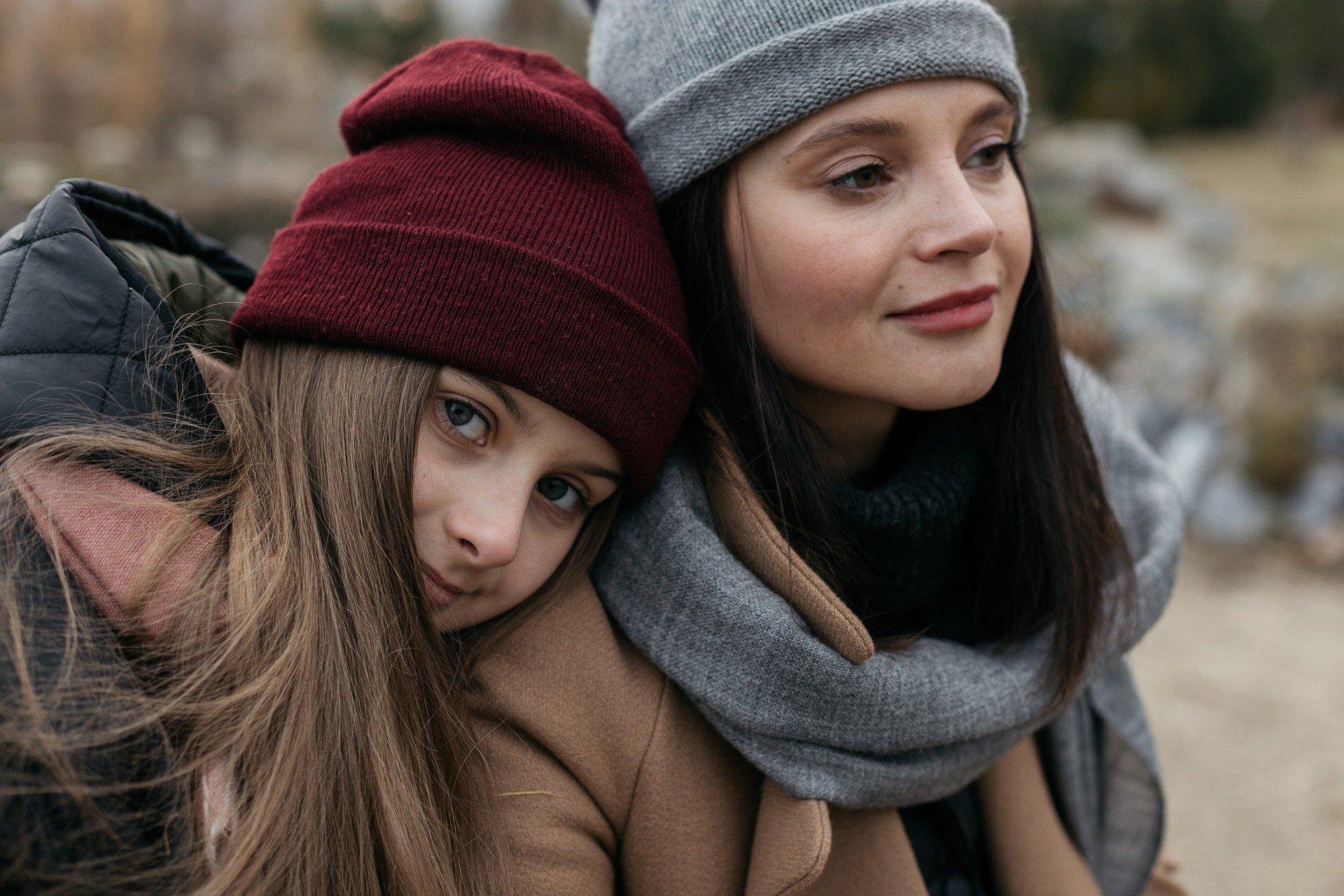 Imagem de duas moças abraçadas com roupas de frio.
