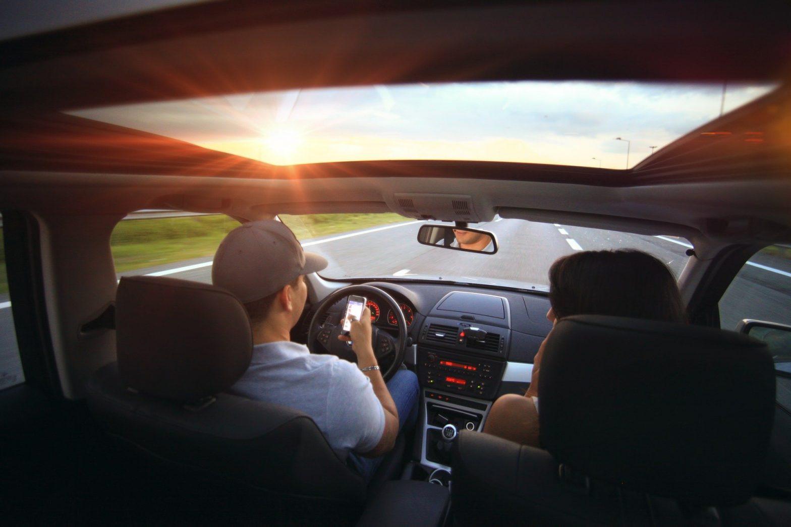 Foto de duas pessoas em um carro no meio da estrada. Imagem ilustrativa para o texto seguro auto barato.
