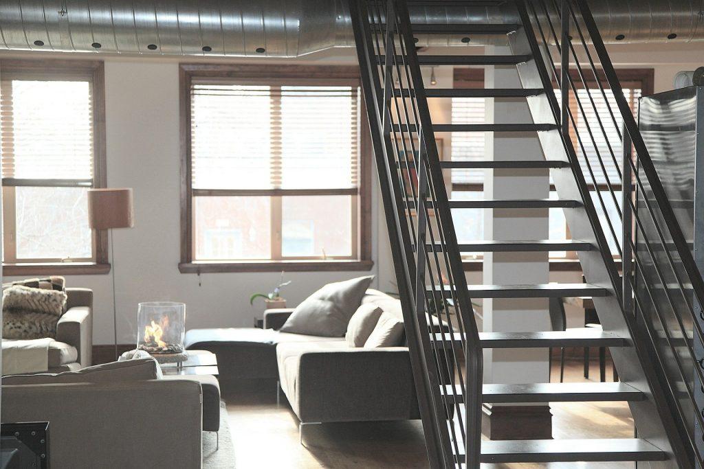 Foto da parte interna de uma casa, com escada, sofás, janelas e demais móveis.