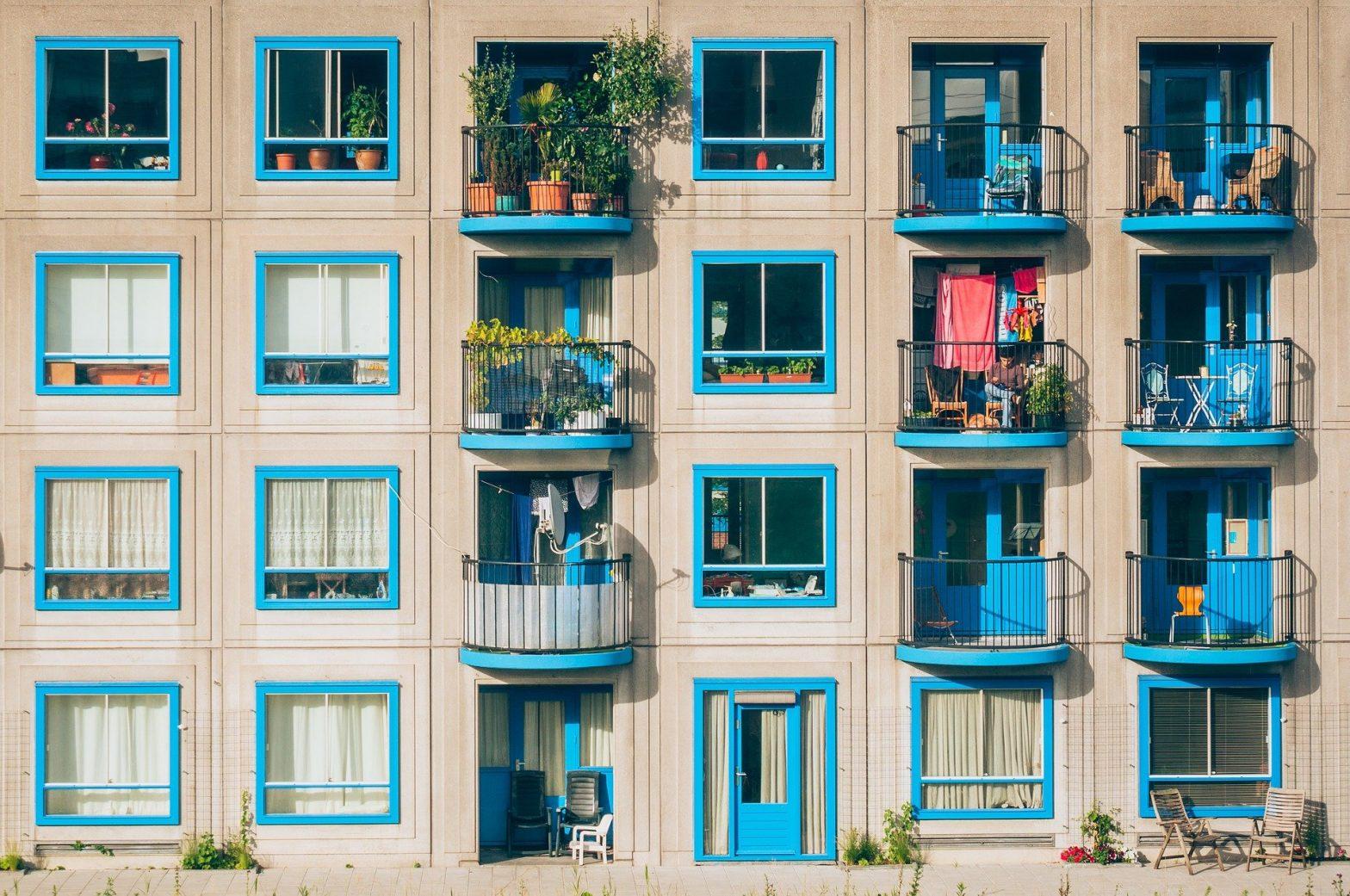 Foto da parte externa de um prédio com vários apartamentos coloridos. Imagem ilustrativa para o texto seguro condomínio.