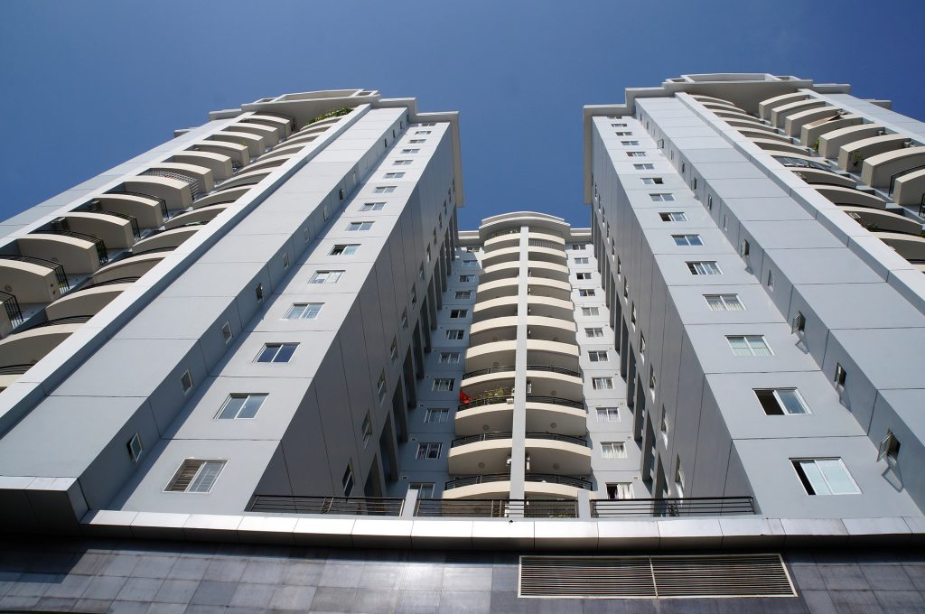 Foto de baixo para cima de um prédio azul com vários apartamentos. Imagem ilustrativa para o texto seguro condomínio.