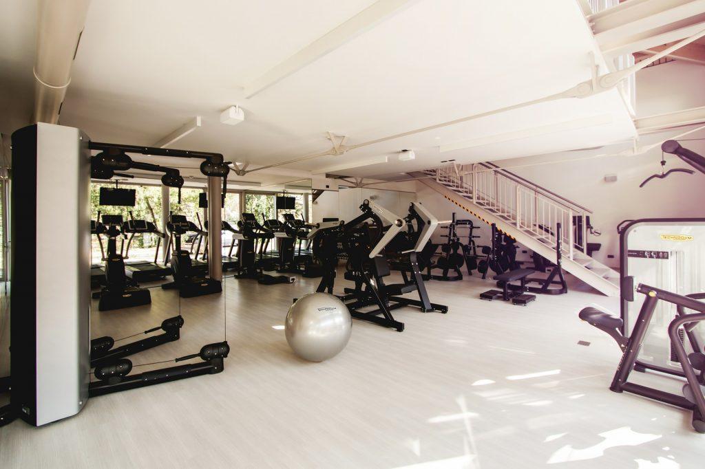 Foto de uma academia em um prédio, com vários equipamentos espalhados.