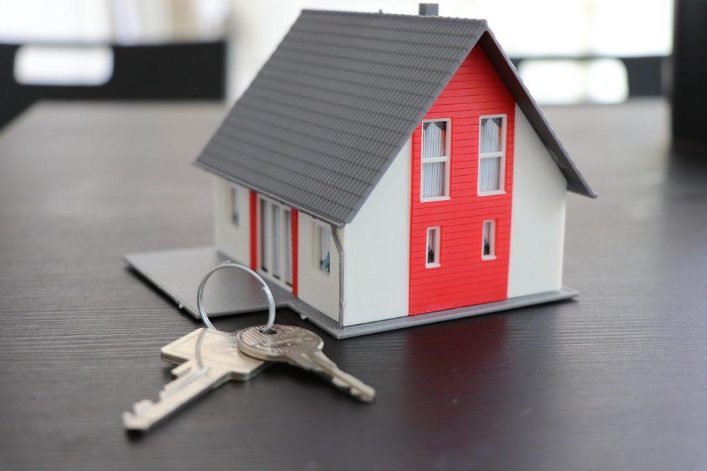 Foto da miniatura de uma casa vermelha, com uma chave ao lado.