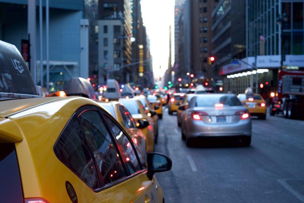 Foto de vários carros em uma avenida movimentada, com prédios ao redor. Imagem ilustrativa para texto seguro obrigatório.