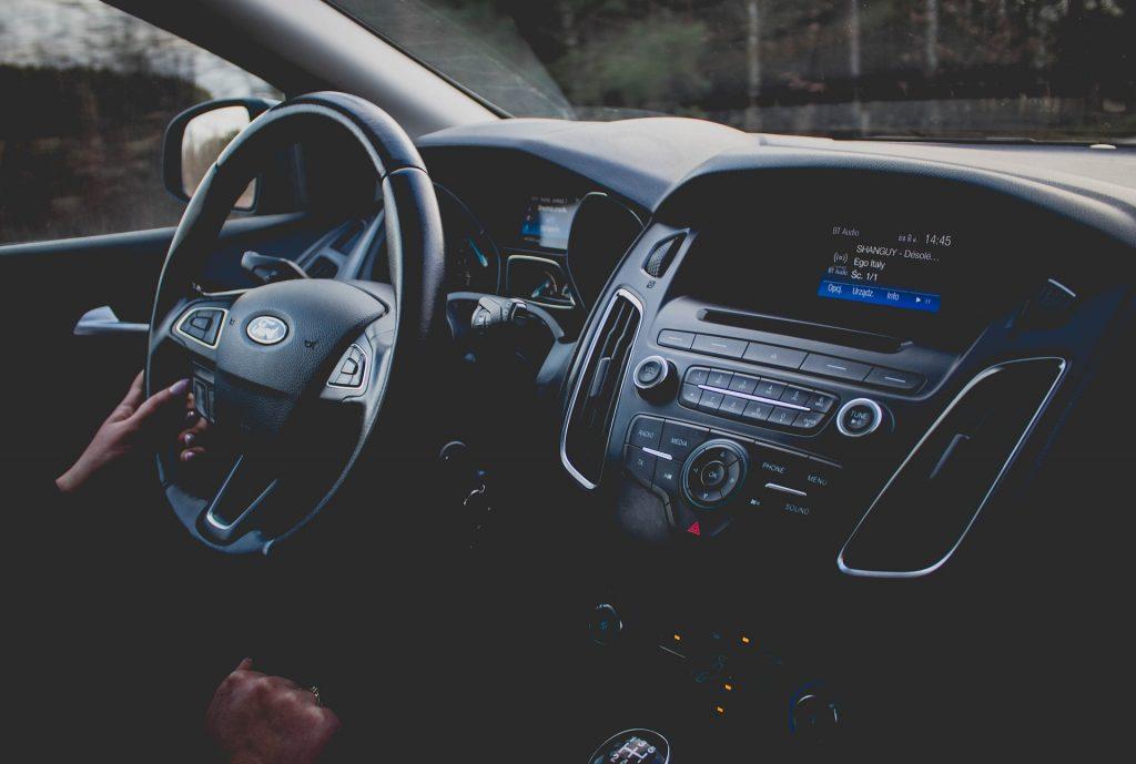 Foto do painel de um carro, ao lado vemos a mão de uma pessoa segurando o volante. Ilustração do texto sobre seguro obrigatório.
