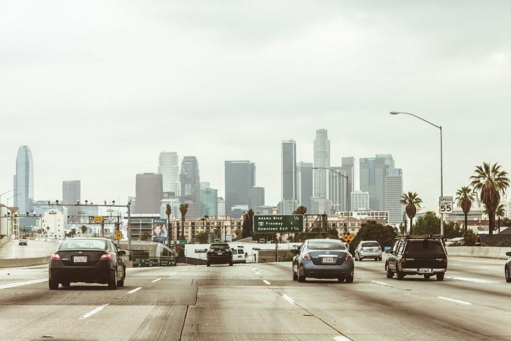 Foto de vários carros em uma avenida, com prédios ao fundo. Imagem ilustrativa para o texto seguro obrigatório.