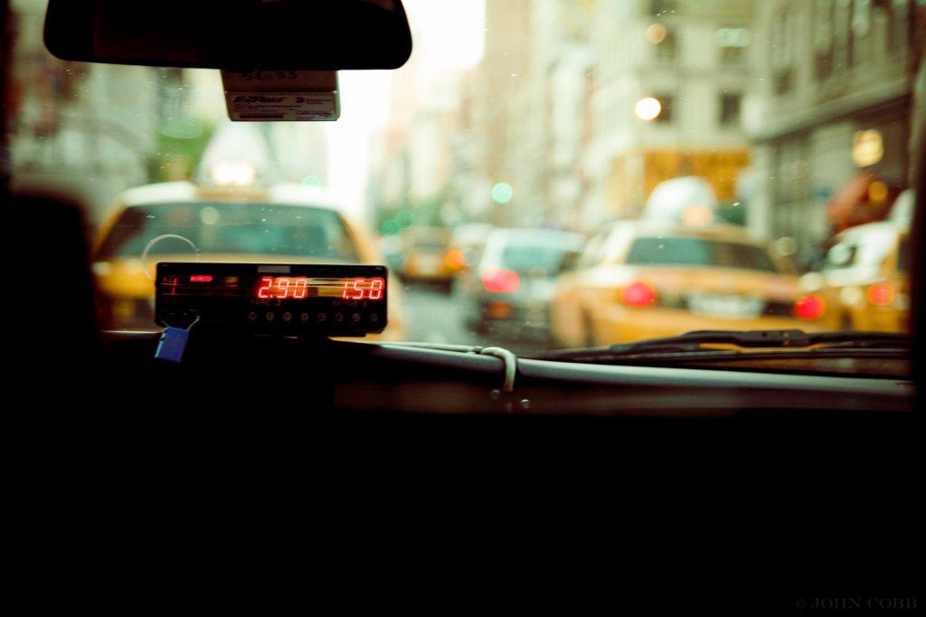 Foto da parte interna de um táxi, com a vista de uma rua movimentada na frente. Imagem ilustrativa para texto seguro para táxis e ubers.