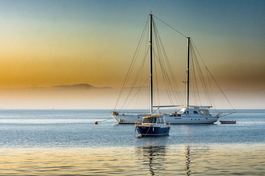 Foto de um barco preto e outro branco em um mar amplo. Temos a luz laranja do sol e névoa. Imagem ilustrativa para texto seguros obrigatórios.
