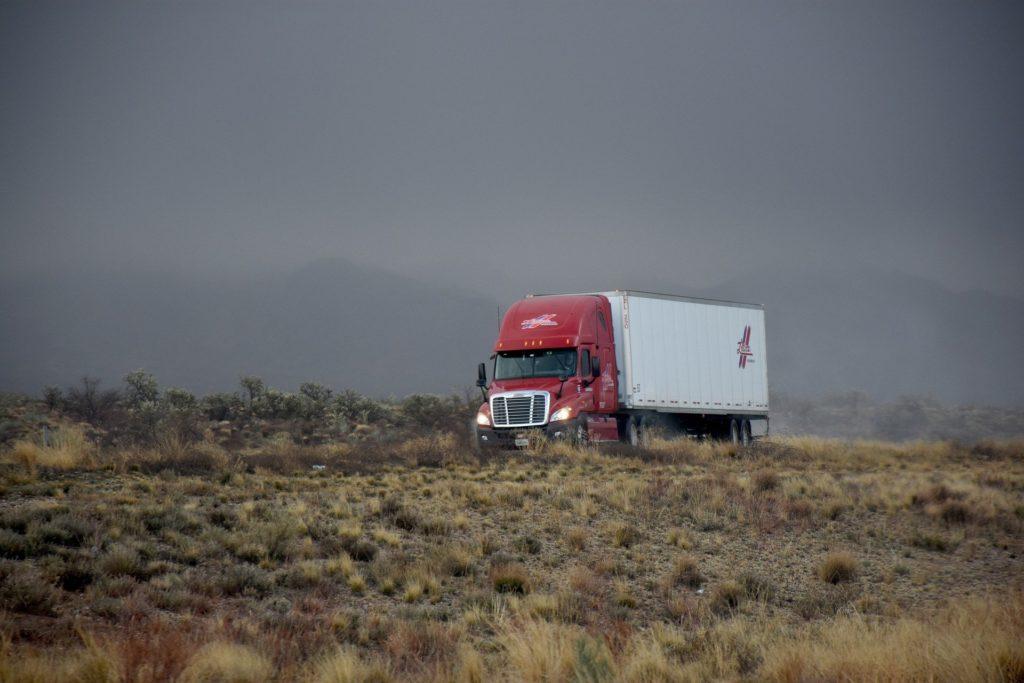 Foto de uma caminhão vermelho e branco em uma estrada com várias plantas ao redor. Ao fundo a paisagem é escura. Imagem ilustrativa para texto seguros obrigatórios.