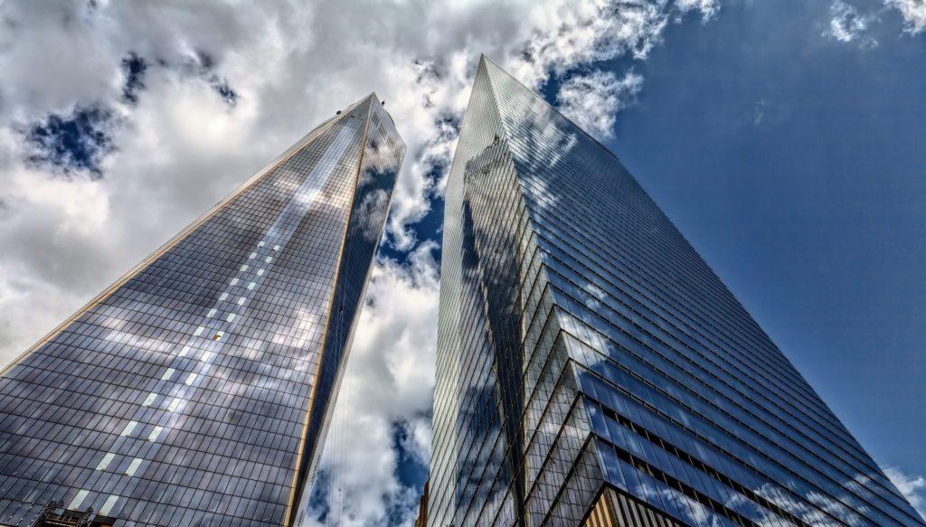 Foto de dois prédios altos e espelhados contra o céu.