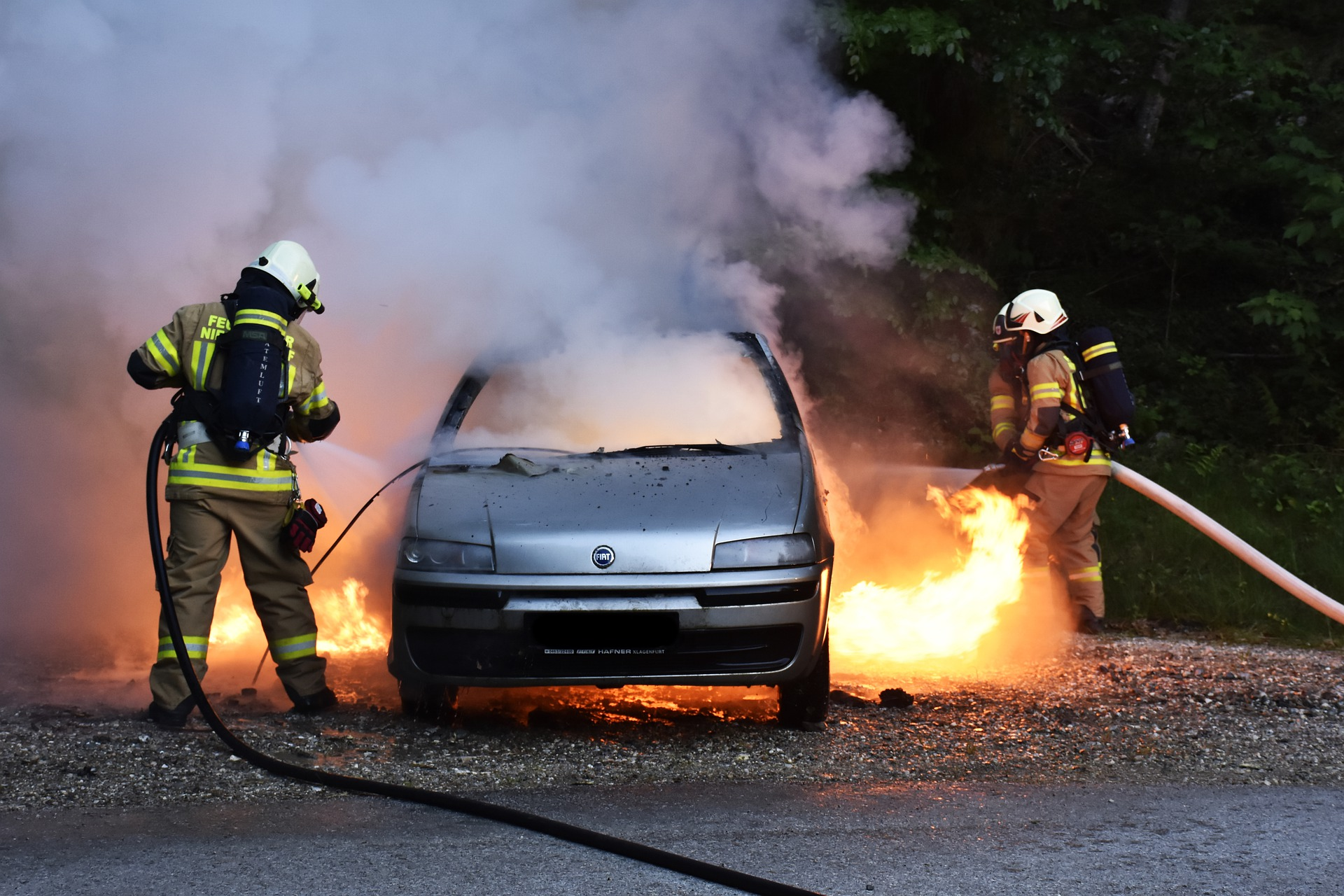 Foto de bombeiros apagando fogo em um carro no meio da rua. Imagem ilustrativa para o texto incêndio e vandalismo.