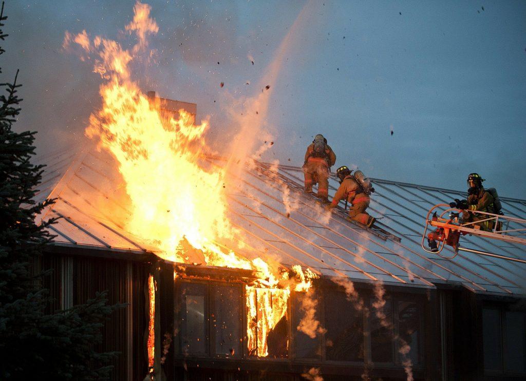 Foto de bombeiros apagando fogo em uma casa. Imagem ilustrativa para o texto incêndio e vandalismo.