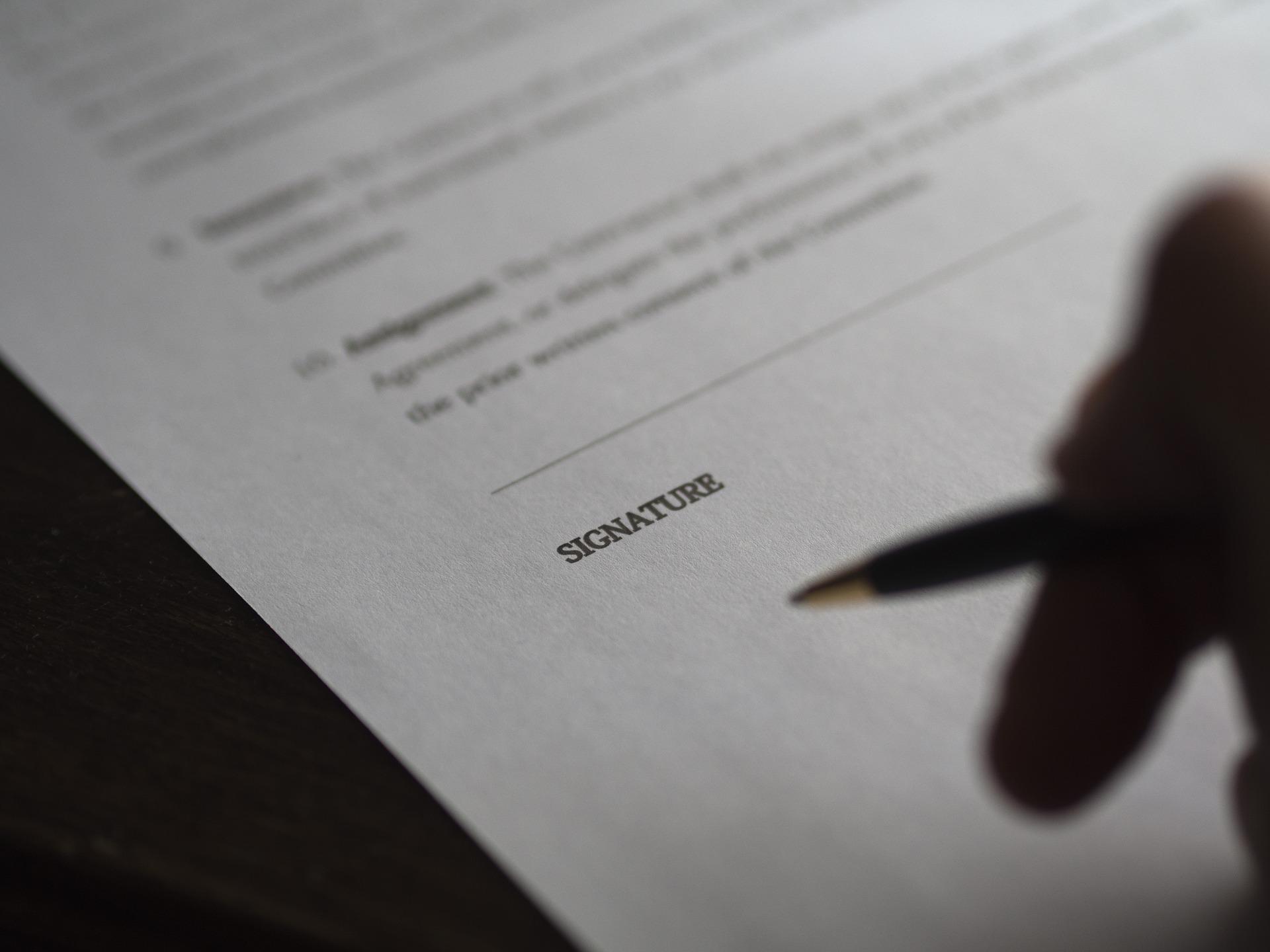 Foto da mão de uma pessoa com uma caneta, próximo de um contrato.  Imagem ilustrativa para o texto incêndio e vandalismo.