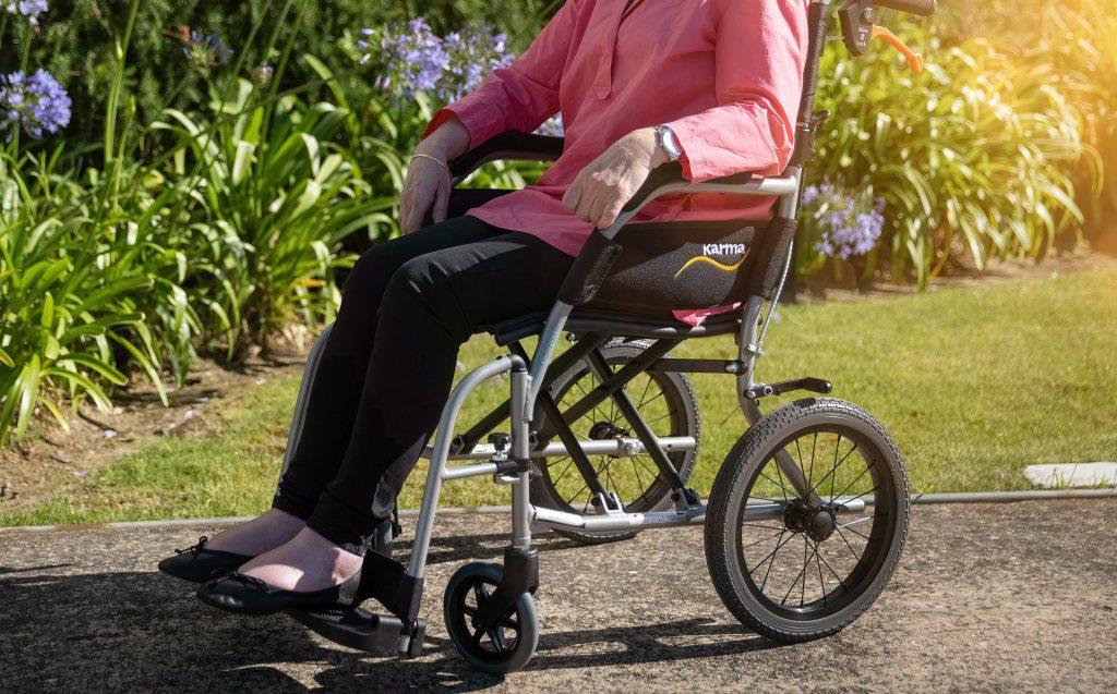 Foto de uma mulher em uma cadeira de rodas, com plantas ao fundo. Imagem ilustrativa para o texto seguro auto para deficiente físico.