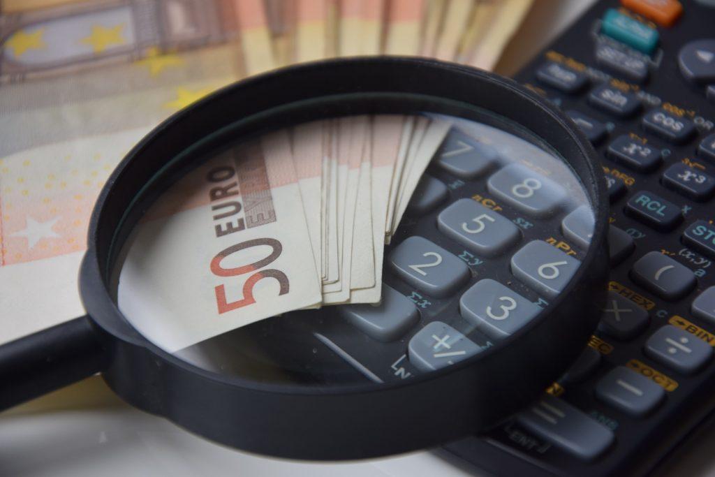 Foto de uma lupa com notas de dinheiro e uma calculadora. Imagem ilustrativa para o texto valor da franquia do seguro.