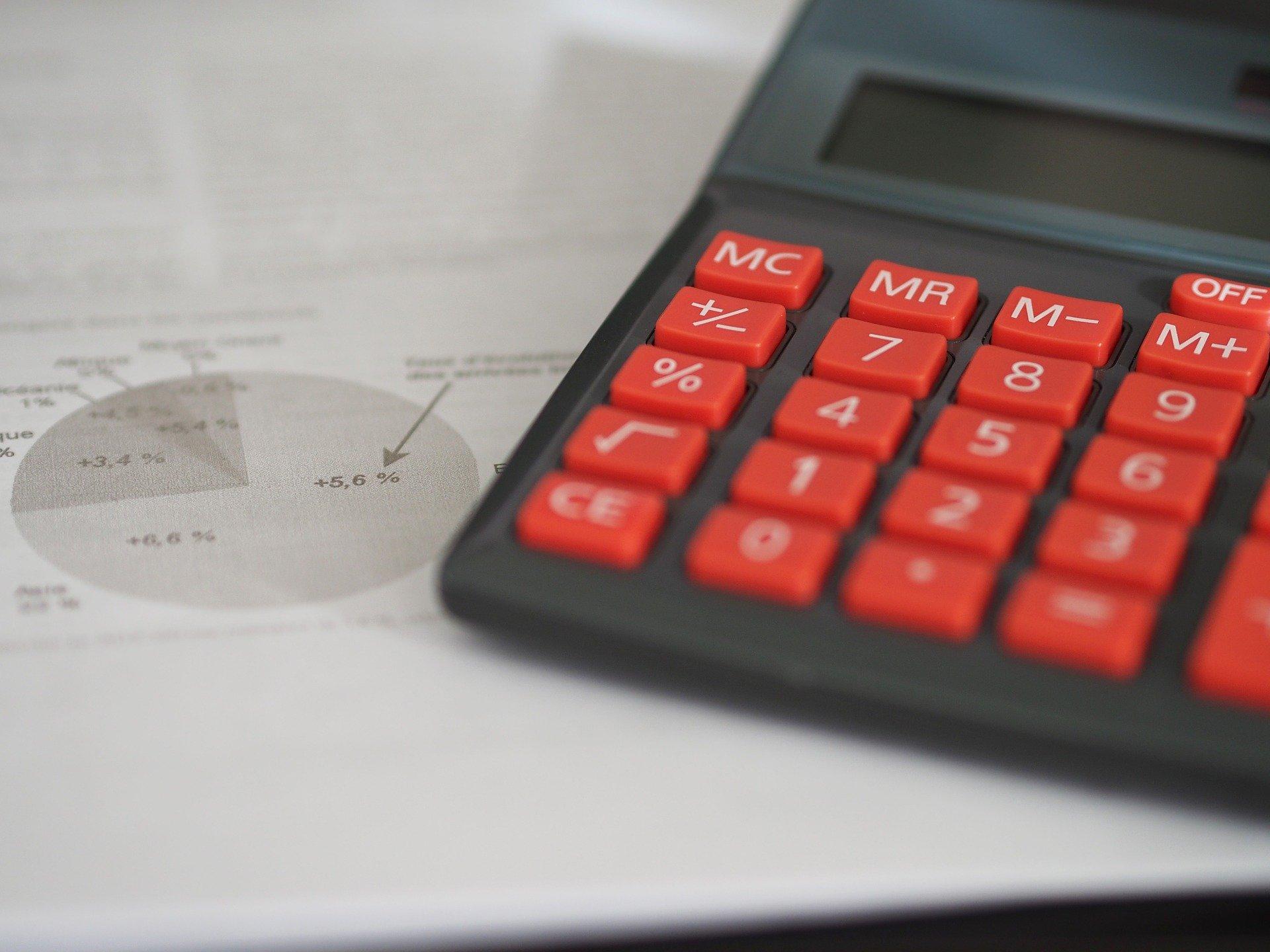 Foto de uma calculadora preta e vermelha ao lado de um papel com gráficos. Imagem ilustrativa para o texto valor da franquia do seguro.