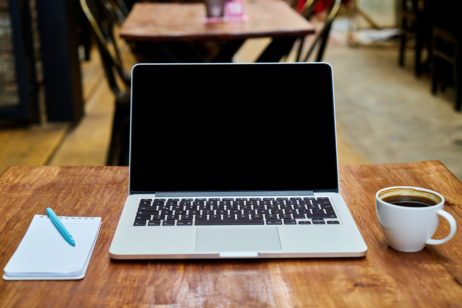 Foto de uma mesa com um computador, xícara de café e um caderno. Imagem ilustrativa para o texto valor da franquia do seguro.