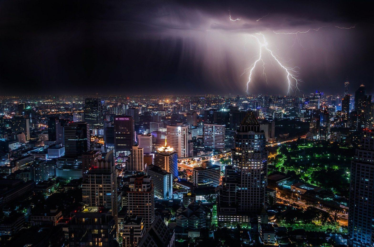 Foto de uma cidade e uma tempestade com raios caindo. Imagem ilustrativa para o texto seguro contra intempéries.