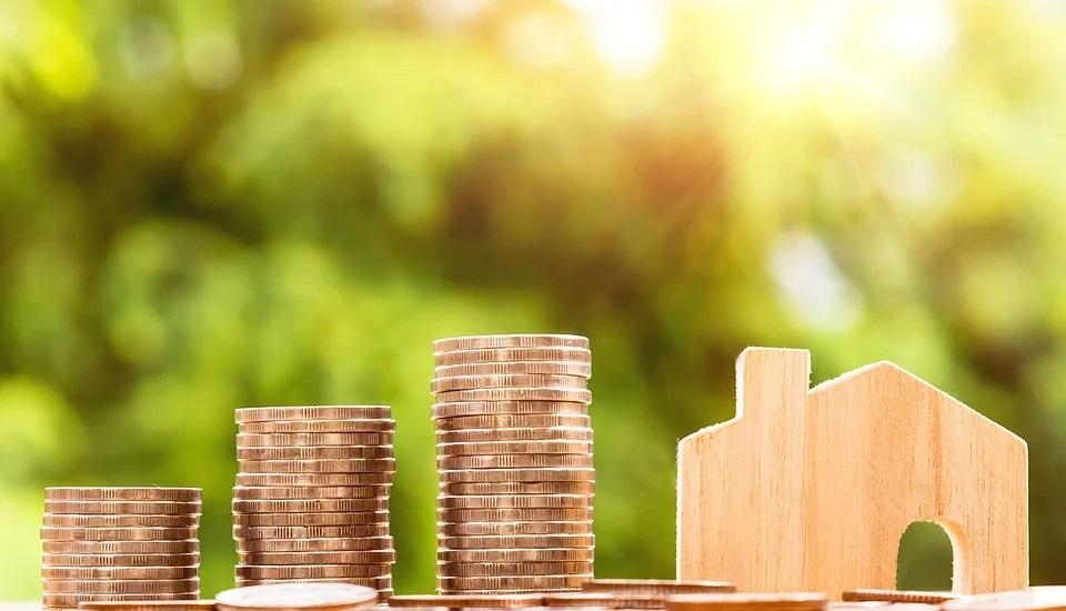 Foto da miniatura de uma casa ao lado de pilhas de moedas. Imagem ilustrativa para o texto melhor consórcio do Brasil.