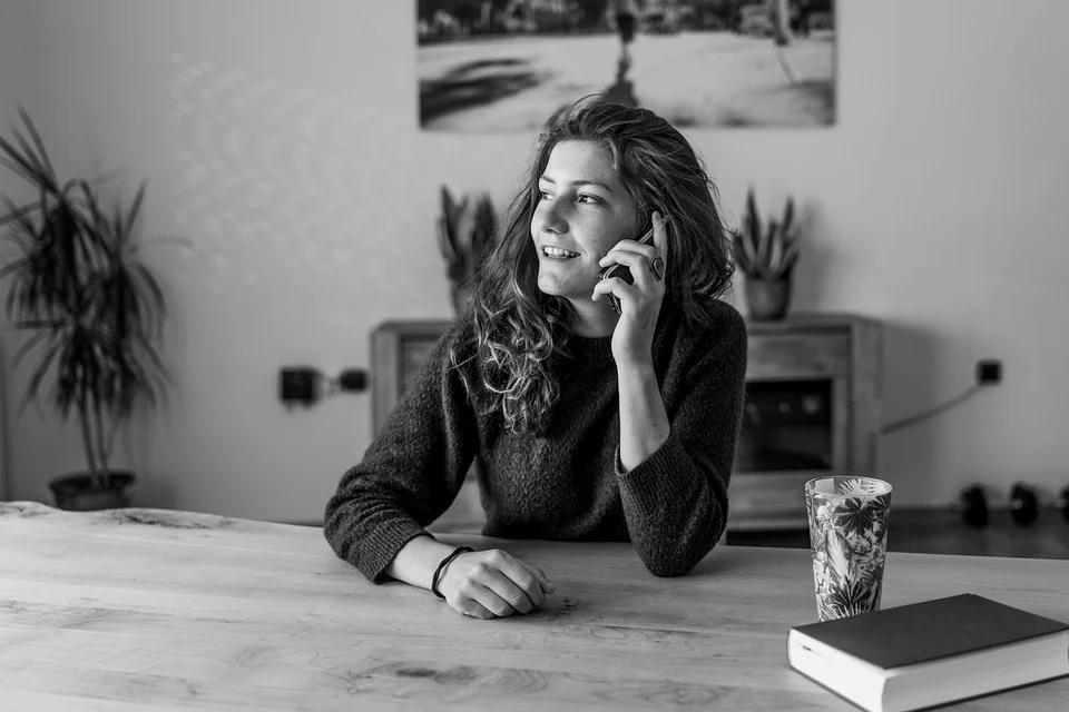 Foto de uma mulher na sala com telefone. Imagem ilustrativa para o texto melhores franquias do Brasil.